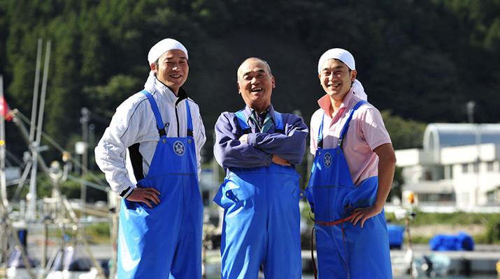 男性三人が笑顔でこちらを向いている